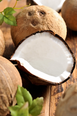 sliced coconut flesh and whole coconuts Banco de Imagens
