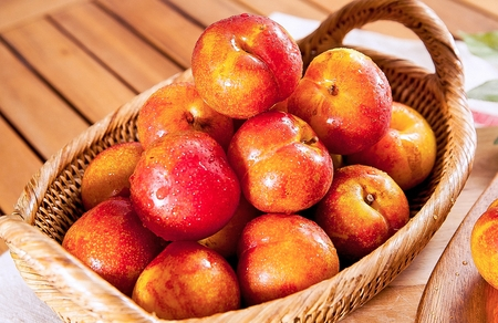 fresh plums with drops in woven basket