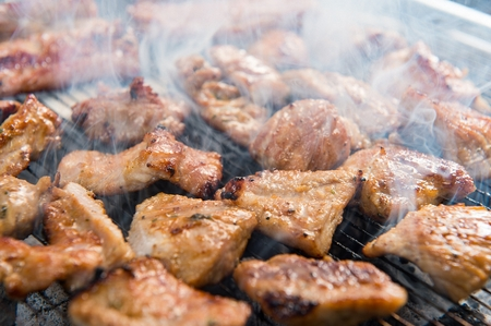 Marinated pork spareribs being grilled on grill Stock Photo