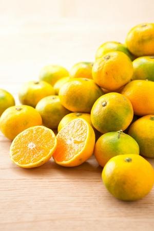 sliced and whole mandarins, tangerine fruits on wood floor