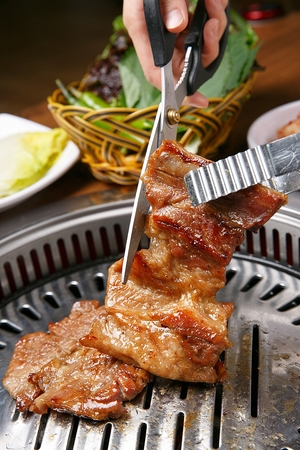 Pincers and scissors cutting marinated pork spareribs being grilled on stainless grill