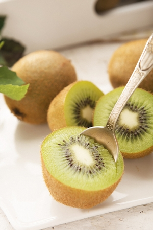 halved kiwi scopped using spoon