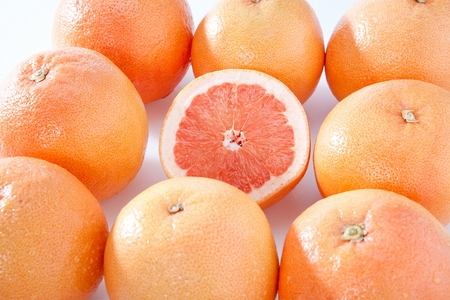 halved grapefruit surround by whole grapefruits 写真素材 - 122842163