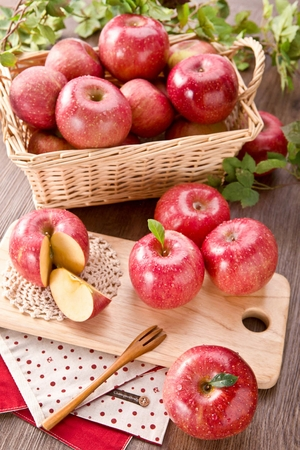 bunch of fresh red apples in basket and on wood chopping board, creative concept