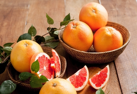 sliced and whole grapefruits on table with leaf decorations