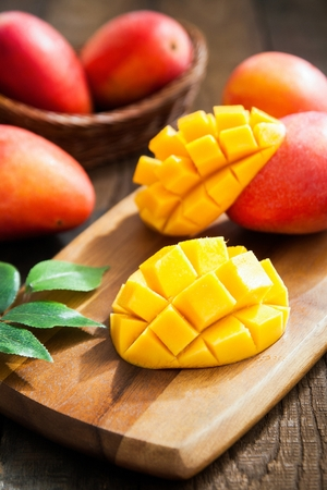 Sliced apple mango on cutting board Imagens