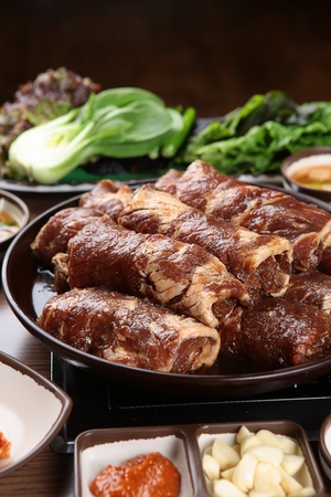 Raw marinated pork spareribs on plate, with side dishes