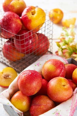 fresh plums with drops in paper box and plastic net container Stock Photo