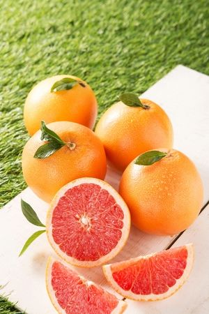 sliced and whole grapefruits on wood panel, artificial grass
