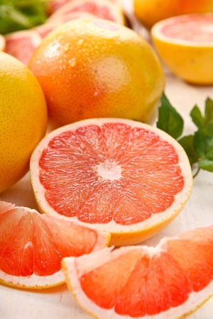 sliced and whole grapefruits on table