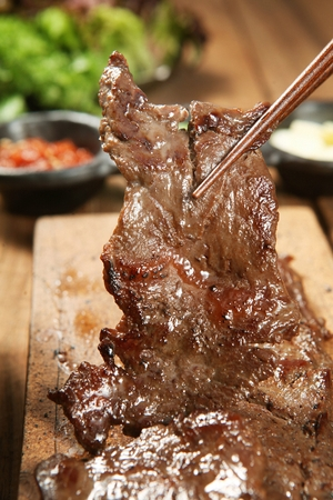 Chopsticks grabbing grilled marinated pork spareribs from wooden cutting board Stock Photo