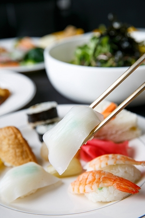 Chopsticks grabbing dried cuttlefish sushi among various kinds of sushi on white plates