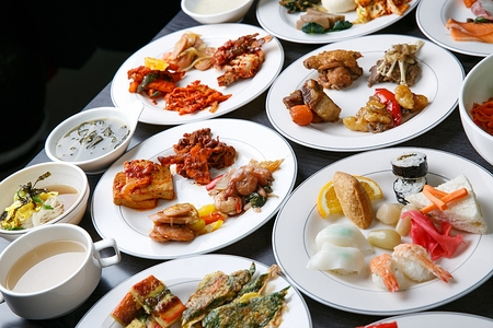 A table full of buffet food such as korean pancakes, sushi, marinated crab and braised pork ribs
