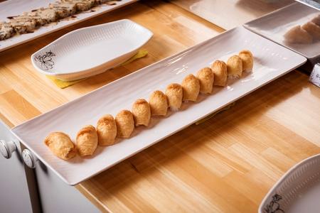 Fried tofu rice balls arranged in one line on rectangular plate, buffet background Stok Fotoğraf