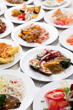 A table full of buffet food such as stir-fried glass noodles and vegetables, raw beef, spaghetti and braised pork ribs, on white plates