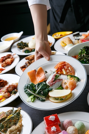 A table full of buffet food such as stir-fried glass noodles and vegetables, korean pancakes, salads, salmon, on white plates