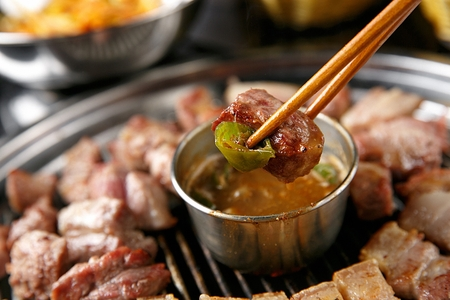 grilled black Samgyeopsal, pork belly and chili from anchovy sauce on chopsticks