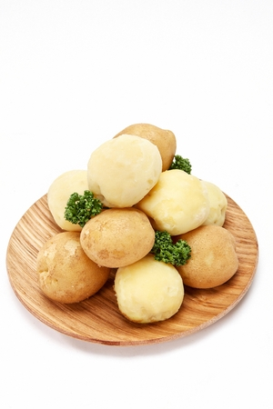 potatoes and peeled off potatoes on round wood plate, white background