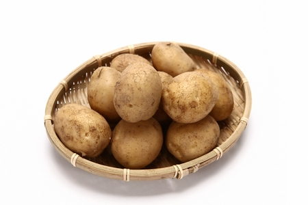 potatoes in woven basket, white background