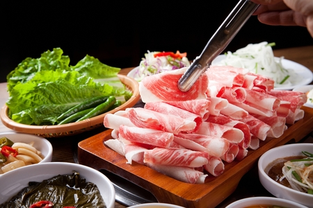 raw thin pork belly on tongs, barbecue setting