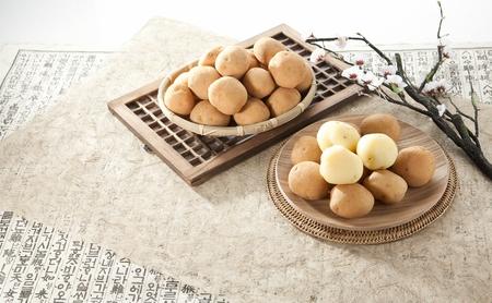 Jerusalem artichokes in woven basket and potatoes on wood plate