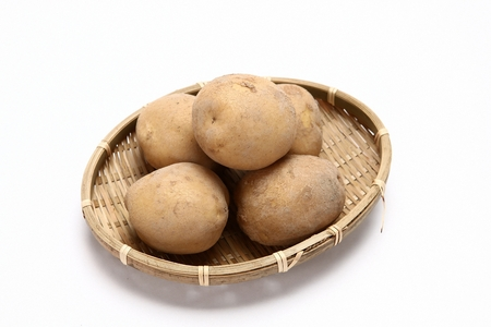 five potatoes in woven basket, white background