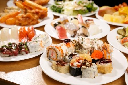 Ein Tisch voller Speisen vom Buffet wie Sushi, Salat, gekochtes Schweinefleisch und gebratene Schweinekoteletts auf weißen Tellern