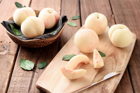 whole and sliced white peaches and knife on chopping board