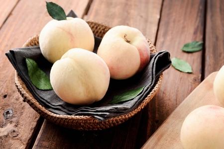 three white peaches in woven basket