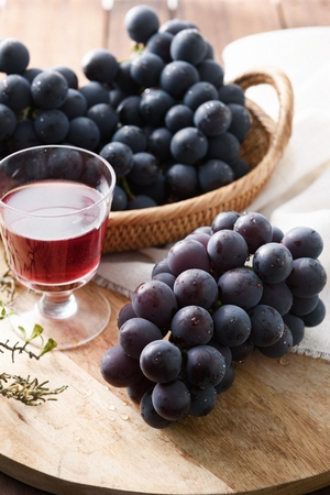 grapes and grapejuice on wood tray and woven basket