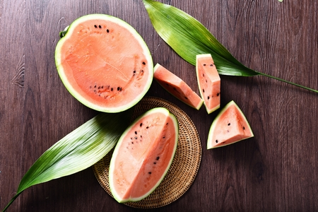 sliced water melon with seeds with leaf decorations, top view