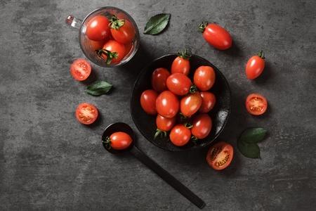 cherry toamtoes on ceramic bowl on black table 写真素材