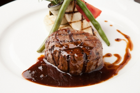beef tenderloin steak with asparagus, tomatoes and mushrooms, on round plate 스톡 콘텐츠