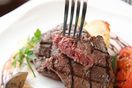 Fork grabbing beef tenderloin steak, from white plate