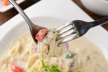 Fork grabbing cream pasta with broccoli and tomatoes, on rectangular plate Reklamní fotografie