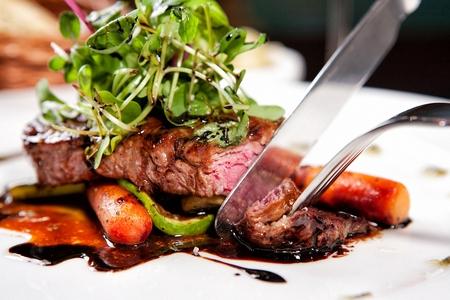knife cutting beef tenderloin steak with carrots, sweet pumpkin and broccoli