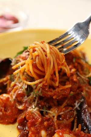 Fork grabbing arrabiata pasta with mussels and shrimp, on yellow plate Reklamní fotografie