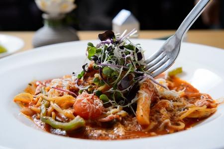 Horquilla agarrando espaguetis ala Amatriciana con brotes, sobre placa blanca.
