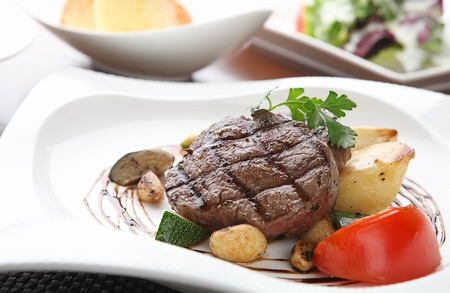 beef tenderloin steak with tomatoes and potatoes on white plate