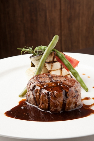 beef tenderloin steak with asparagus, tomatoes and mushrooms, on round plate