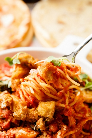 Fork grabbing arrabiata pasta with fried meat, on white plate