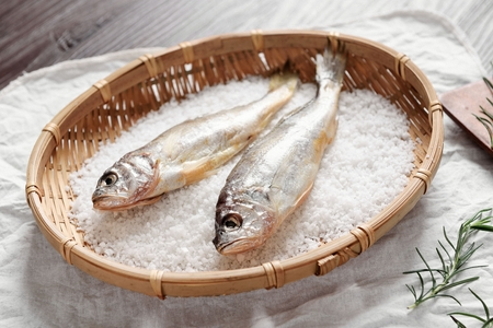 salted dry fish on wooden basket