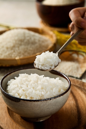 spoon scooping up rice from rice bowl, and rice in basket and small container