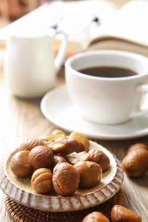 peeled chestnuts on round plate, and a cup of coffee