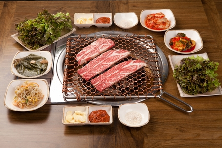 a table full of side dishes such as kimchi and seasoned bean sprouts, together with raw beef on gridiron