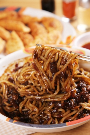 chopsticks grabbing black bean sauce noodles from round plate
