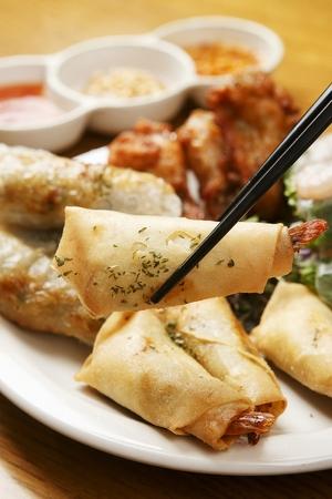 chopsticks grabbing cha gio from white plate