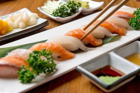 baguettes saisissant des sushis au saumon d'un assortiment de sushis Banque d'images
