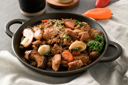 braised spicy chicken with glass noodles and vegetables, on round plate with handles