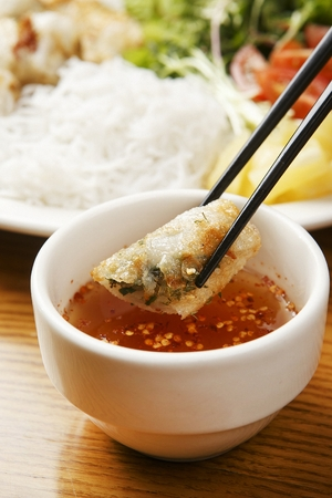 chopsticks dipping cha gio in sauce Stock Photo